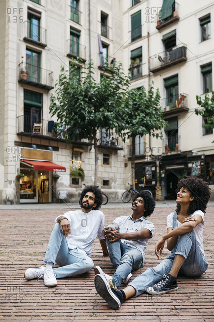 Spain- Barcelona- three friends sitting on a square looking up