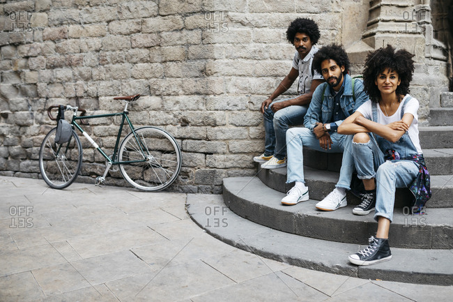 Group of three friends sitting together on stairs in the city