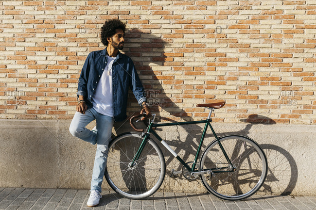 Young man with racing cycle leaning against brick wall