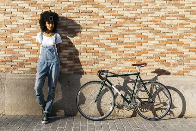 Woman with racing cycle leaning against brick wall