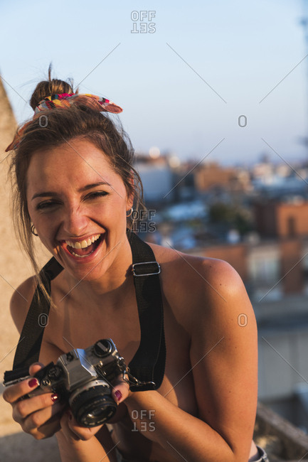 Laughing topless young woman with camera on balcony
