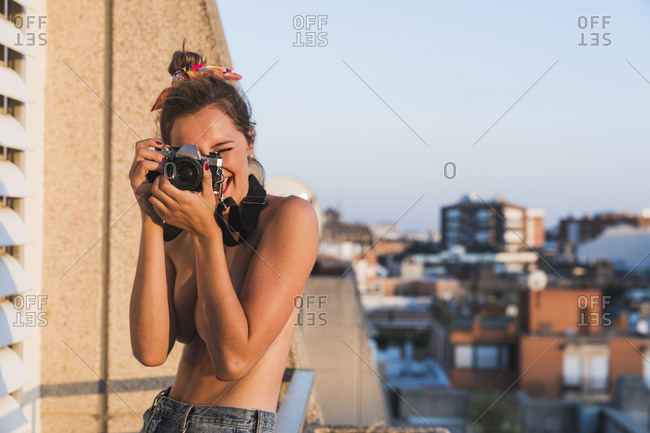 Happy topless young woman with camera taking pictures on balcony