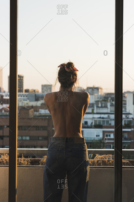 Rear view of topless young woman standing on balcony