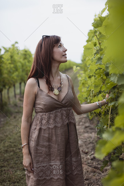 Woman standing in vineyard- wearing summer dress