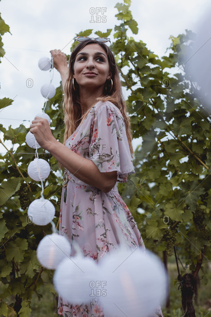 Young woman decorating vineyard with fairy lights for a picnic