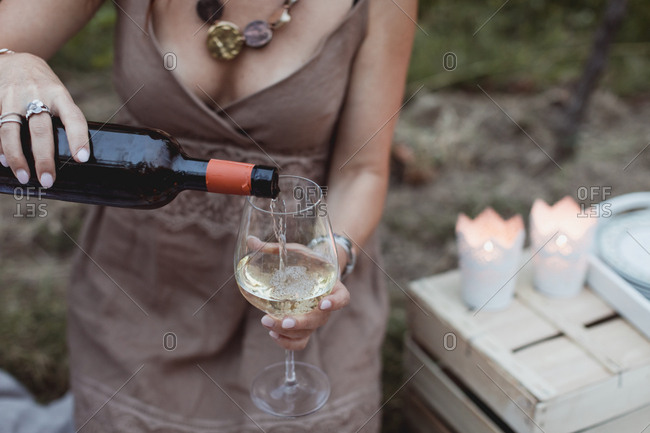 Woman pouring wine in glass on a picnic in nature