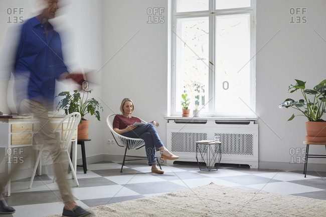 Mature woman reading magazine at home with man passing by
