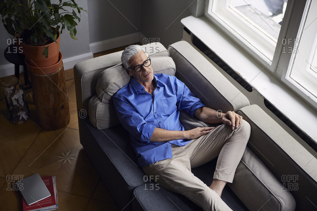 Pensive mature man on couch at home