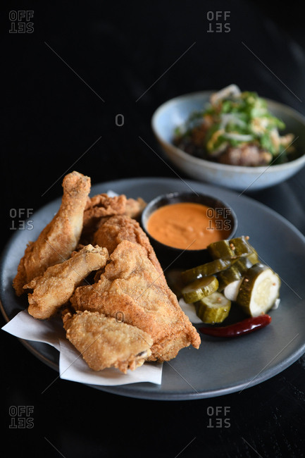 Fried chicken pieces served with pickles and sauce