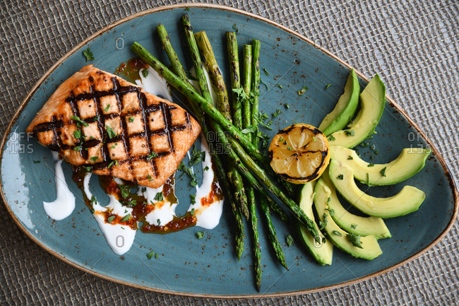 Grilled salmon served with asparagus and avocado slices
