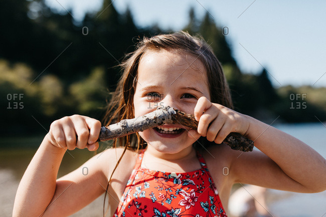 Portrait of a girl holding a stick next to her face while playing outside in nature