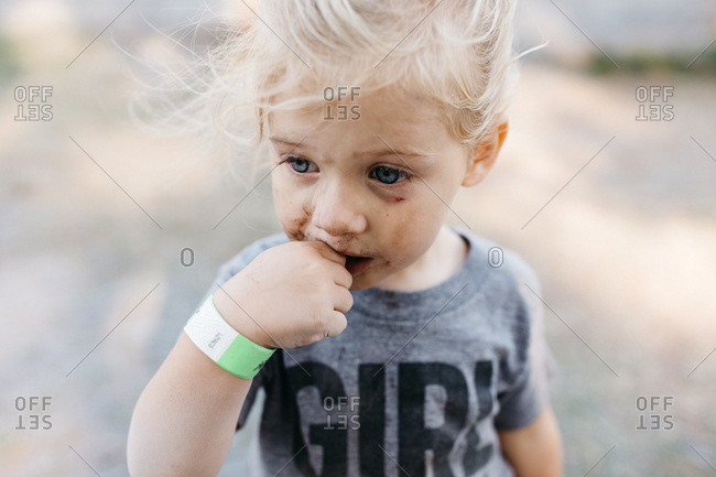 Portrait of a girl with a muddy face sucking her thumb
