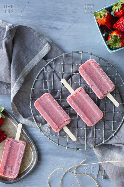 Overhead view of strawberry popsicles with fresh strawberries