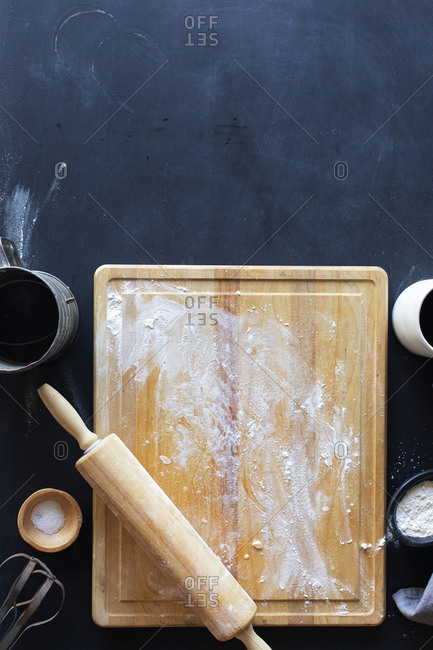 Remnants of pie dough on a wooden cutting board with rolling pin