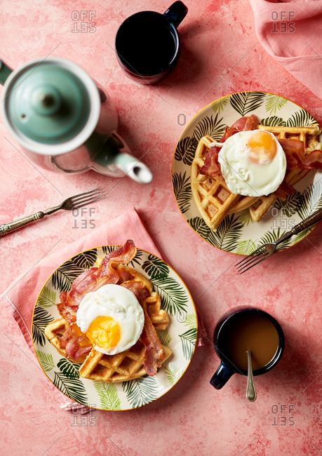 Top view of a waffles with bacon and eggs for two