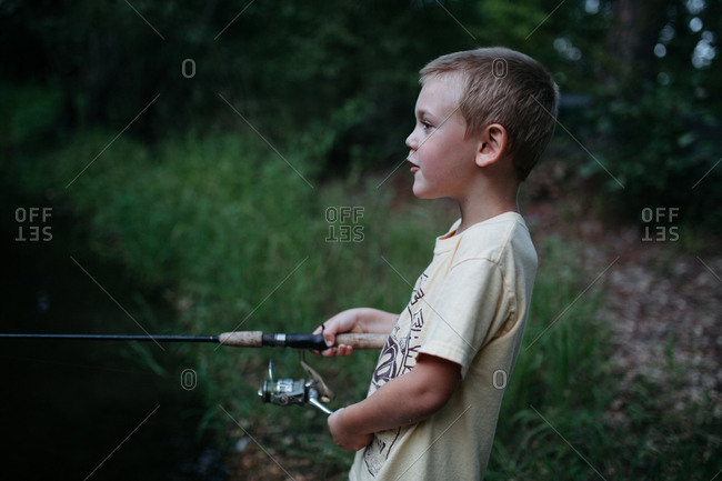 A boy stands by a body of water, fishing