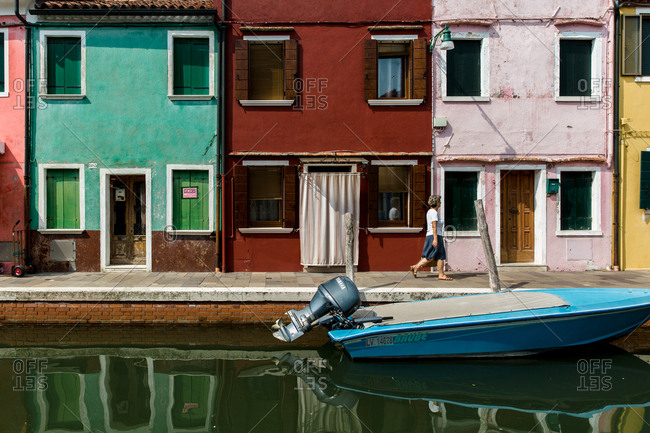 Burano, Venice, Italy - August 8, 2018: Woman walking beside canal