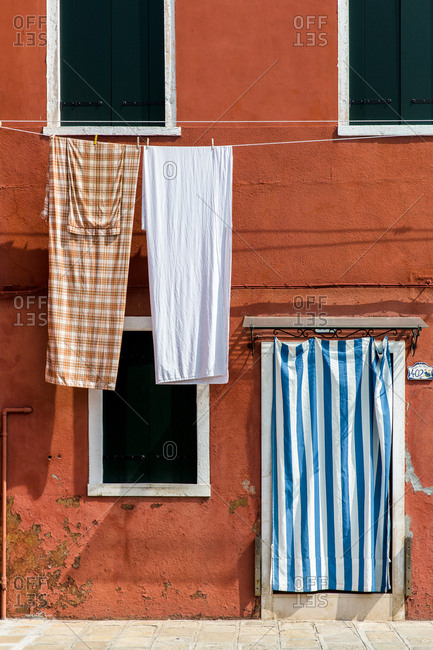 Burano, Venice, Italy - August 8, 2018: Clothesline with sheets on building in Italy