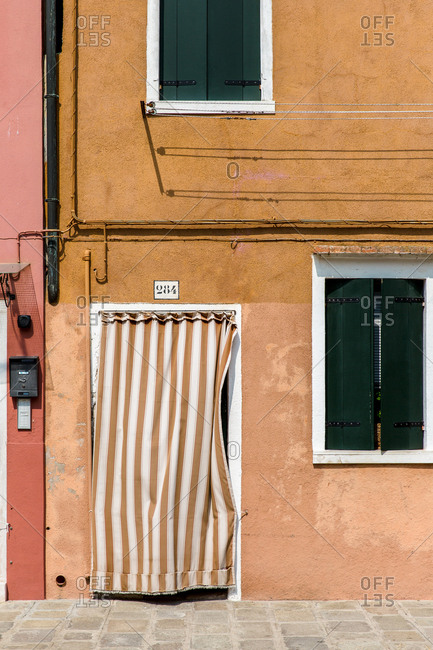 Burano, Venice, Italy - August 8, 2018: Striped curtain on doorway of building