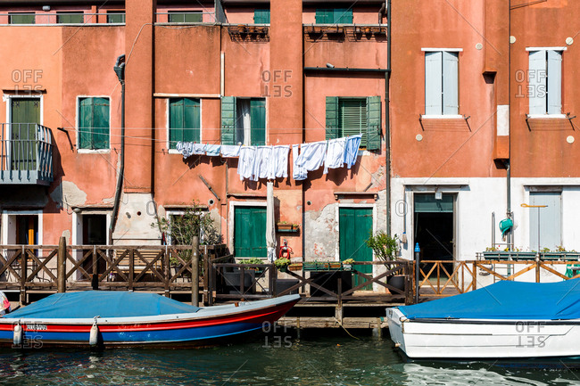 Venice, Italy - August 9, 2018: Boats in canal beside building with clothesline