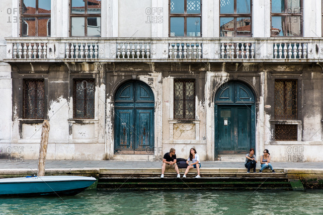 Venice, Italy - August 8, 2018: People sitting on steps along a canal in Venice