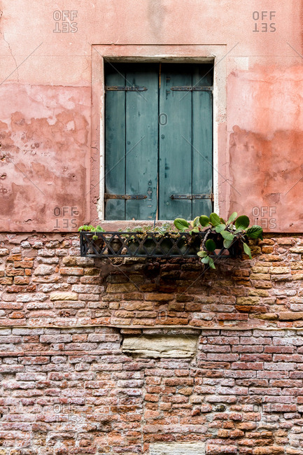 Window on building with closed shutters and planter box in Venice, Italy
