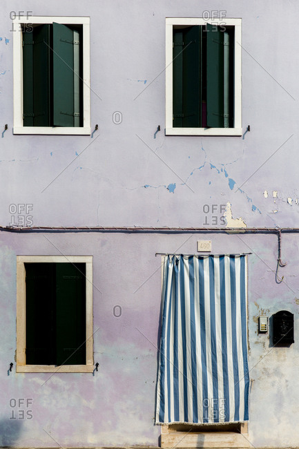 Burano, Venice, Italy - August 8, 2018: Striped blue curtain on doorway of building