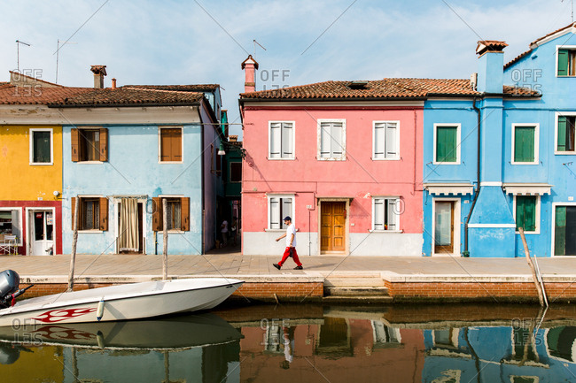 Burano, Venice, Italy - August 8, 2018: Man walking along canal in Burano