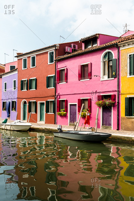 Burano, Venice, Italy - August 8, 2018: Brightly colored homes along a canal in Burano