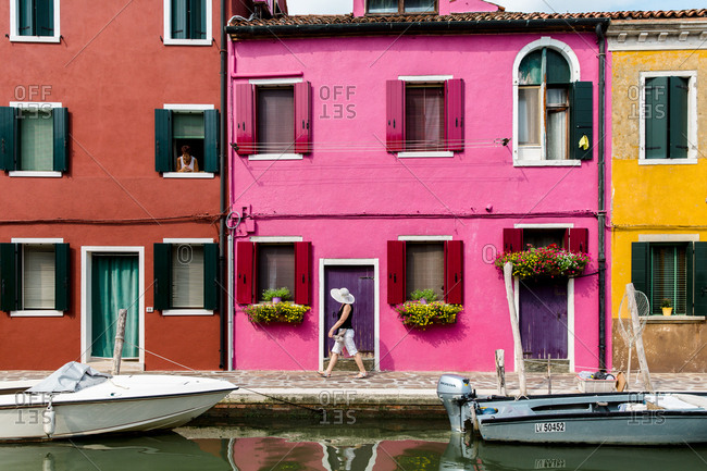 Burano, Venice, Italy - August 8, 2018: Person walking in front of colorful homes in Italy