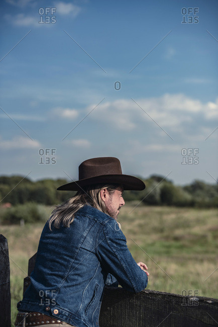 Man in cowboy hat leaning on fence looking out to countryside