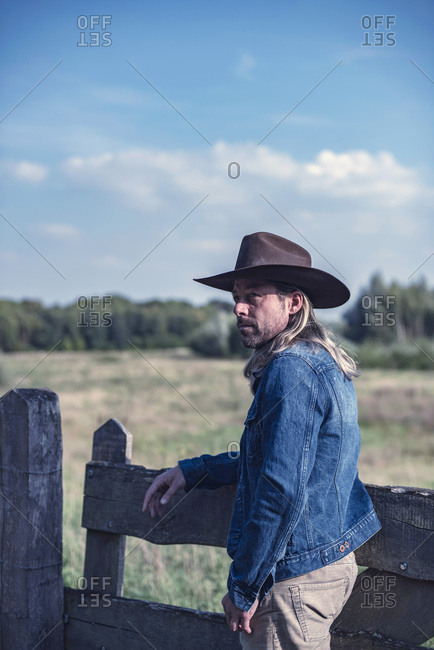 Man in cowboy hat leaning on fence looking away