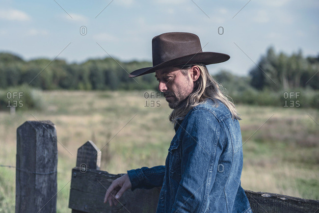 Man in cowboy hat leaning on fence looking down