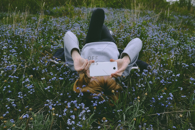 Young woman resting in a field holding cell phone