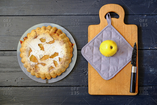 Overhead view of a pie beside a cutting board with a yellow apple