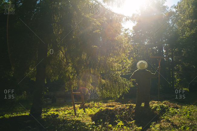 Rear view of person standing in sunlight with yard tool