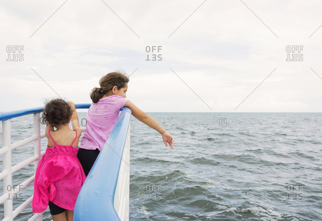 Two sisters watching the ocean from the railing of a boat