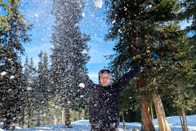 Boy with outstretched arms throwing snow outdoors