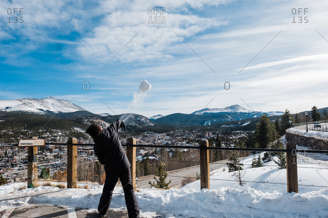 Boy throwing snowball off of scenic overlook