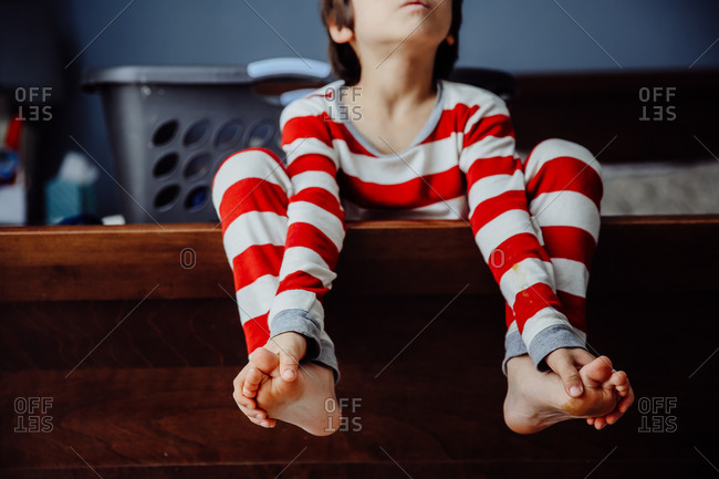 Boy in striped pajamas dangling his bare feet over side of bed