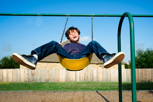Laughing boy on swing set at park
