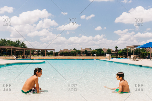 Two boys sitting in shallow water of swimming pool looking at each other