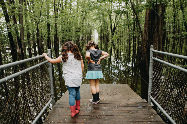 Two girls looking over a fenced path at  the swamp