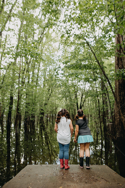 Two girls looking into the swamp
