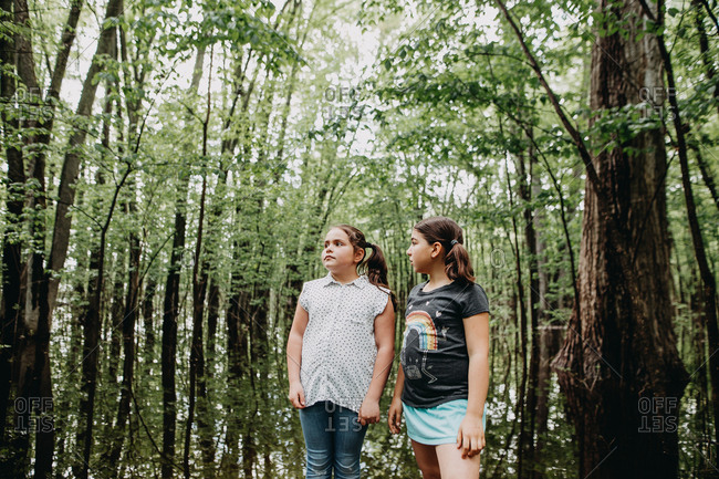 Two young girls standing in lush marshland