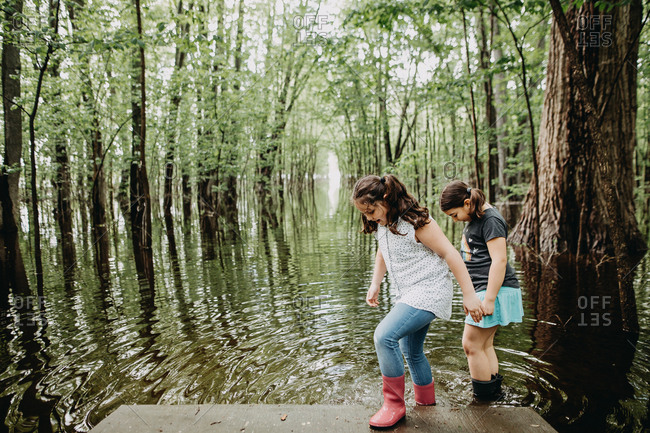 Two girls playing at the waters edge of a lush marshland