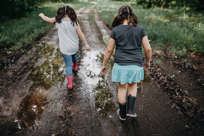Two girls walking down a muddy path