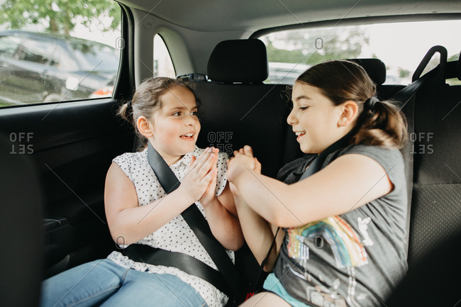 Two girls playing hand clapping games in the backseat of a car