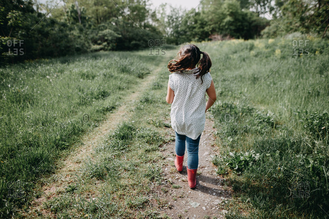 Young girl walking down a nature path