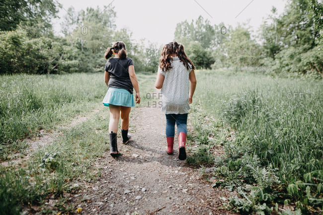 Two girls walking down a lush path